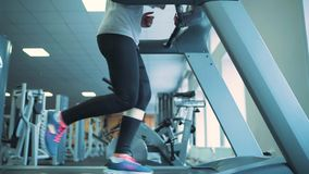 Woman running on treadmill in gym. Young woman running on treadmill in gym stock video footage