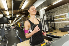 Young woman running on the treadmill and listening to music at t Royalty Free Stock Images
