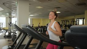 Young woman is running on treadmill at sports club. Female jogging. Young woman is running on treadmill at sports club. Female jogging stock video footage