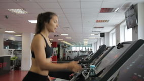 Young woman running on treadmill in sports club indoors. atlete walks stock video footage