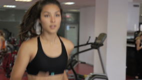 Young woman running on treadmill in sports club indoors. Female is training hard in spacious gym, jogging. Attractive brunette run muscles of human body stock footage