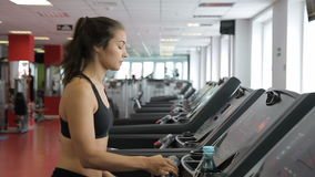 Young woman running on treadmill in sports club indoors. stock footage