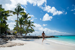 Young woman running at the tropical beach Stock Photo