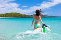 Young woman running into tropical blue sea with Royalty Free Stock Photos