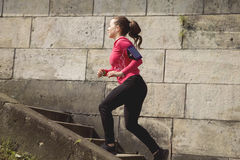 A young woman running up the stairs in a park. Royalty Free Stock Image