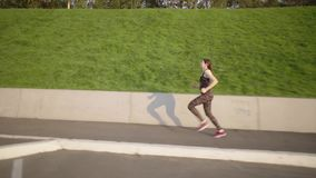 Young woman running on urban area. Athletes running in an urban environment near a parking on background of green hill. Sports woman in dark tracksuit engaged in stock video