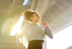 Young woman running in urban environment. Portrait of a young woman running in urban environment Stock Images