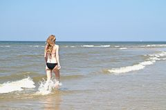 Young woman running through the water Royalty Free Stock Photo