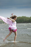 Young woman running through the water at the beach stock image