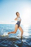 Young woman running in the water with volleyball Royalty Free Stock Image