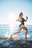 Young woman running in the water with volleyball Royalty Free Stock Photography