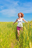 Young woman running through a wheat field Stock Images