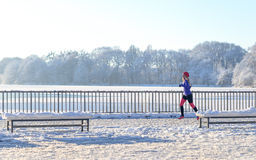 Young woman running in winter snow. Along a promenade overlooking the ocean as she enjoys the invigorating cold weather in a healthy active lifestyle concept Stock Photo