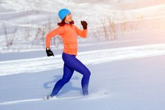A young woman running winter Stock Photos