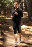 Young woman running on woods, outdoor background Stock Photography