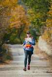 Young woman runs across road in autumn forest Stock Photos