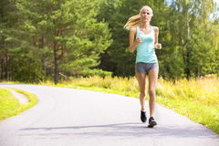 Young woman runs alone outdoor in the forest Stock Image