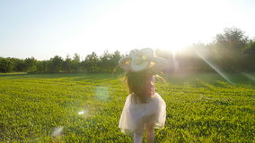 A young woman runs along a green glade at sunset stock footage
