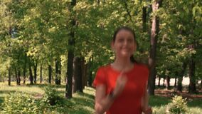A young woman runs along a path on the camera.Smiling, happy.