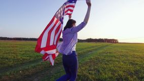 Young woman runs with an USA flag across a field at sunset rear view. Young woman runs with an American flag across a field at sunset rear view stock footage