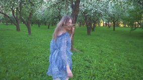 Young woman runs in an apple orchard in the spring flowers white. Portrait of a beautiful girl in the evening fruit stock video