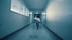 A young woman runs away from her pursuer along a dark corridor