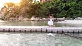 Young happy pretty woman in white dress runs on bridge among the sea on tropical island during beautiful sunset. Young woman runs on bridge among the sea on stock video