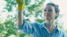 Young woman runs green wet sponge squeegee on dirty window stock video footage