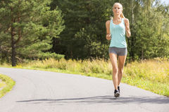 Young woman runs outdoor in the forest. Healthy and slim blonde woman runs or jogs on a road in the forest. Workout outdoor a summer evening Stock Photography