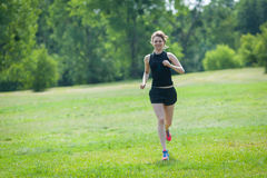 Young woman runs at park. Young woman is running across the grass in the park Stock Photo