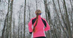 A young woman runs through the park in the winter in a pink jacket. View from the back stock video footage