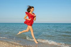 Young woman runs in red dress on the sea Royalty Free Stock Image