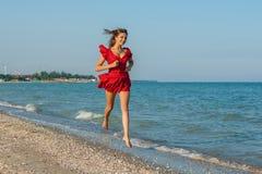 Young woman runs on the sea Stock Photos