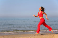 Young woman runs on shore of sea Royalty Free Stock Images