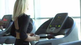 Young woman runs on a treadmill in the gym, slow motion. Close-up stock footage
