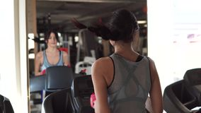 Young woman runs on a treadmill at the gym. the view from the back. Girl running on the treadmill in the fitness room. young woman doing aerobic exercises stock footage