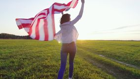 Young woman runs with an USA flag across a field at sunset slow mo. Young woman runs with an American flag across a field at sunset slow mo stock footage