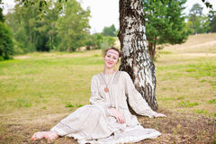 Young woman in the Russian national dress. Young woman in the Russian national dress sitting next to a birch in a field Royalty Free Stock Images