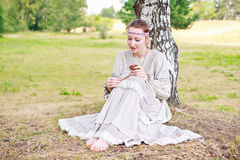 Young woman in the Russian national dress. Young woman in the Russian national dress sitting next to a birch in a field Stock Photo