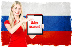 Young woman with russian national flag. On the background holding tablet pc. with sample text in russian language WELCOME stock images
