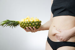 Young woman's body with pineapple Stock Photo