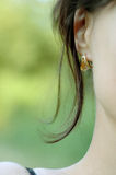 Young Woman's Ear. Closeup of a young woman's ear, partial cheek, neck and shoulder royalty free stock images