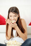 Young woman's eating popcorn. Royalty Free Stock Photography