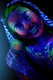 The young woman`s face aliens asleep. The girl`s face, aliens asleep. Hand on the shoulder, ultraviolet make-up. Vertical. Beautiful royalty free stock photography