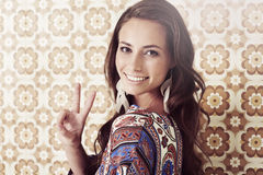 Young woman in 1970's fashion giving peace sign Royalty Free Stock Photos