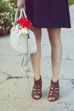 Young woman's feet standing on the path and holding a handbag Royalty Free Stock Images