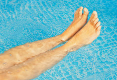 Young woman's feet in a swimming pool Royalty Free Stock Images