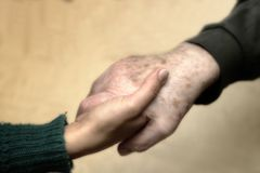 Hand of a young woman shaking that of a senior. A young woman`s hand gripping that of an old man Royalty Free Stock Photos