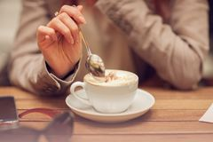 Young woman`s hand holding a spoon, stir a cup of coffee in a street cafe on a wooden table. Can be used as background stock images