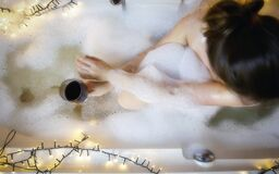 Young woman`s hand holding wine glass in bathtub, drinking red wine and lying in bathtub with bubble foam, top view, relaxtion an